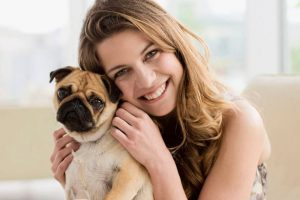 Smiling-woman-holding-cute-small-dog-on-lap
